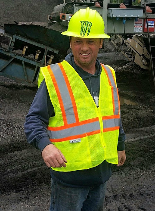 man at construction site wearing yellow construction vest and helmet