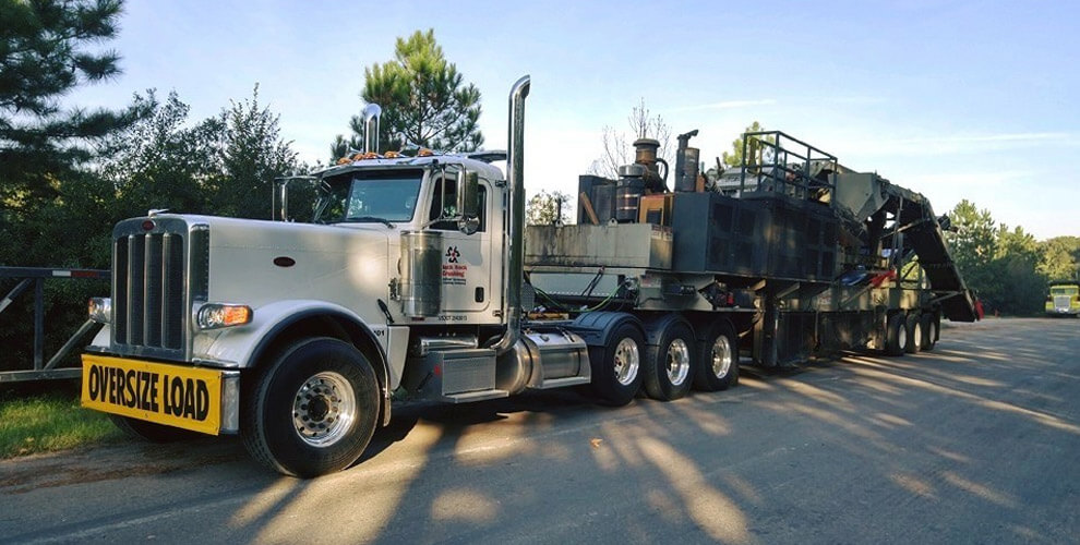 oversize load truck hauling heavy equipment