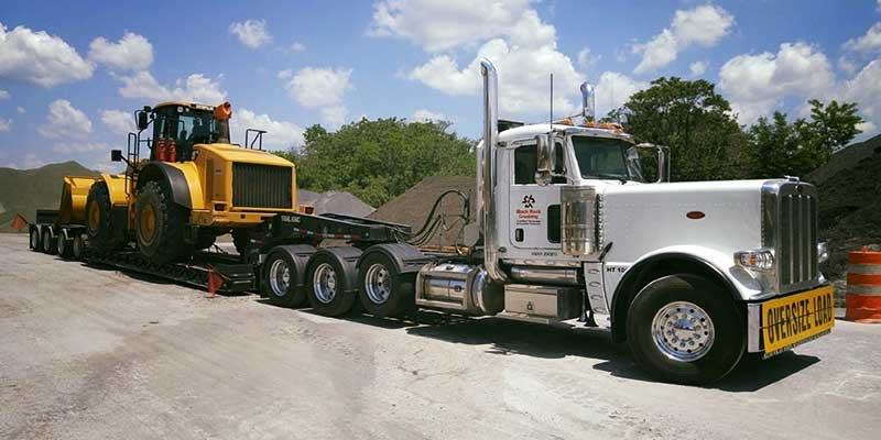 white oversize load truck hauling heavy construction equipment