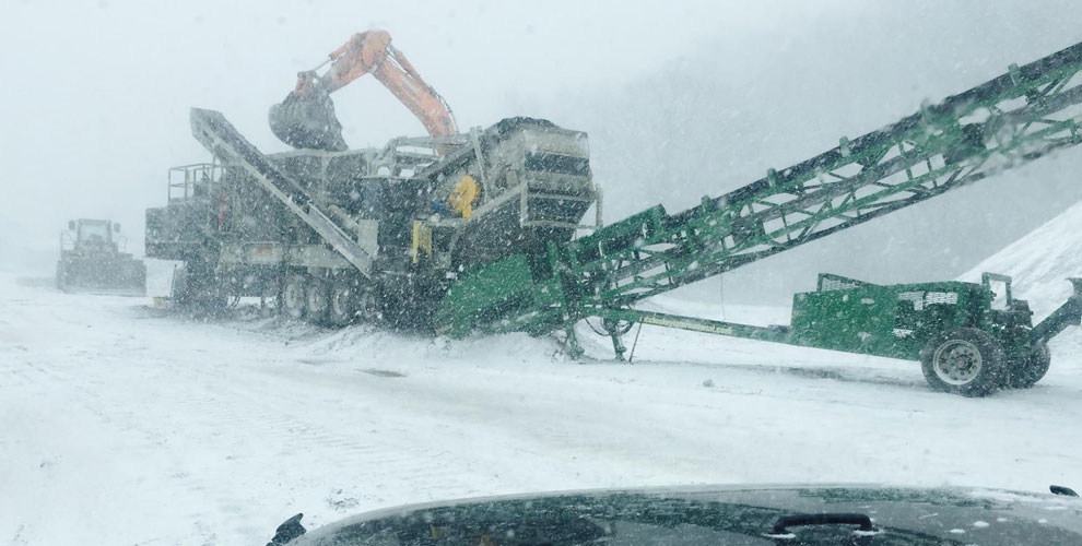 crushing construction equipment in a snow storm